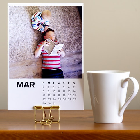 Calendar prints with a gold clip as a stand.