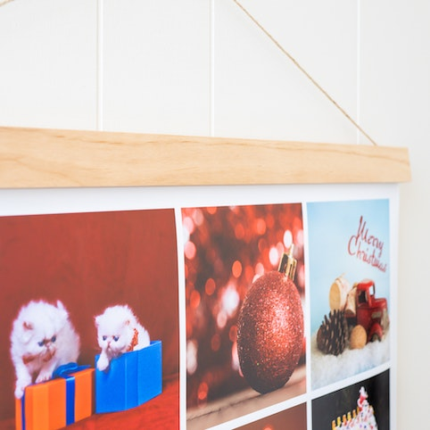 Wooden hanger holding collage poster.